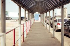 View of empty walkway for passenger walking to embark to boat an. D cars are parked to embarking into ferry boat at pier stock image