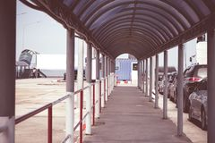 View of empty walkway for passenger walking to embark to boat an. D cars are parked to embarking into ferry boat at pier royalty free stock image
