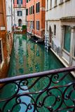 View of empty wooden gondola docked/ parked/ moored beside buildings on narrow water canal from bridge in Venice, Italy stock images