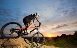 Athlete riding bike and rolling down hill against amazing sky background. royalty free stock photography
