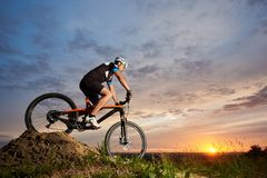 Athlete riding bike and rolling down hill against amazing sky background. stock photography