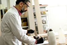 Engineer in the laboratory examines ceramic tiles Royalty Free Stock Images