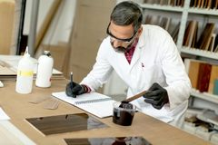 Engineer in the laboratory examines ceramic tiles Stock Photos