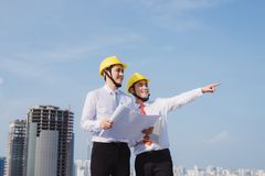 View of a Engineer and worker watching blueprint on construction site stock photography