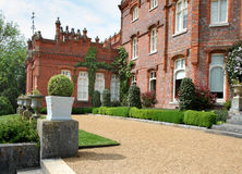 View of an English Manor and Garden. With a row of Ornamental stone Planters set on Plinths Stock Photography