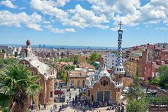View of the entrance of Park Guell, the work of the architect Gaudi full of tourists with the guard house and the stock images
