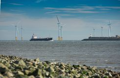 Teeside wind farm and shipping. A view of the estuary of the river Tees , near to Hartlepool and Middlesbrough, Cleveland, County Durham, England. A large ship Royalty Free Stock Photography