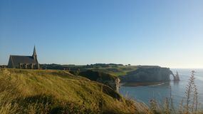View from etretat. The cliffs of Etretat in Normandy and its church bathed in sunshine Royalty Free Stock Photography