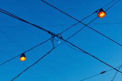 View of new moon crescent through the electric wires on the street with lights which have just been lit royalty free stock images