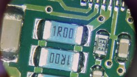 Mounting electrical board under magnification. View through the eyepiece of the microscope of the mounting electrical board. The master moving the board inspects stock footage