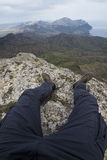 The view from the eyes of the man sitting on top of a mountain. Legs of the man sitting on top of a mountain. The view from the eyes in the first person royalty free stock photography