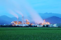 View of a factory in the middle of a green farmland in the early morning twilight. ~ Factory pipes polluting air in a silent morning, a serious environmental Royalty Free Stock Photography