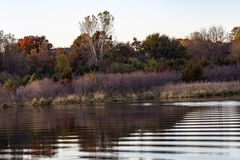 Fall colors in a park with reflections in the lake in Omaha Nebraska. View of fall colors in a park at sunset with reflections in the lake in Omaha Nebraska royalty free stock photos