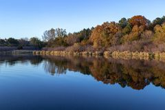 Fall colors in a park with reflections in the lake in Omaha Nebraska. View of fall colors in a park at sunset with reflections in the lake in Omaha Nebraska stock images
