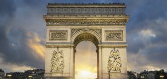View of famous Arc de Triomphe at sunset Stock Photos