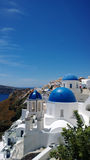 A view of the famous blue dome in Oia on Santorini island. Green tree in the frame. Vertical view Royalty Free Stock Images
