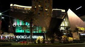 View of a famous boutiques in Las Vegas. View of a famous boutiques and a skyscraper in Las Vegas at night stock footage
