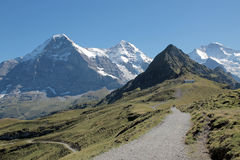 View at the famous Eiger and Jungfrau from Maennlichen Switzerland. Hiking path at Maennlichen with view at the famous Eiger north face, Moench and Jungfrau in royalty free stock photo