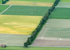 Farming fields and rows of trees with a crop duster plane seen from above stock image