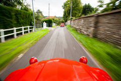 View from a fast-moving Citroen 2CV. Picture taken from inside of a red shiny Citroen 2CV which is driving very fast on a narrow path following another Citroen Royalty Free Stock Photos