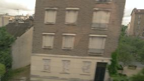 View from fast moving train. Buildings and trees. Close to city limits. All roads lead home stock video footage