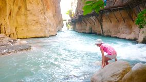 View of fast river in canyon. View of fast river in Saklikent canyon, young woman sits on a stone stock footage