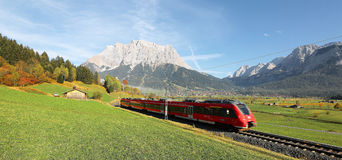 View of a fast train traveling through green fields with magnificent Mountain Zugspitze in the background. On a crisp sunny day in Lermoos, Tirol, Austria ~ stock photography