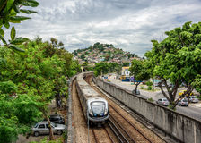 View of favela, grey sky, green trees, railroad tracks and subway train arriving to Inhauma station royalty free stock photo