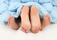 View of feet of couple having sex in bed Stock Image