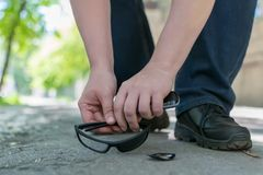 View of the feet of a man and broken sunglasses. View of a man`s feet on a city street that stands on an asphalt pedestrian road and raises fallen and broken royalty free stock photography