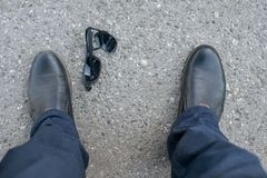 View of the feet of a man and broken sunglasses. View of the feet of a man who stands on an asphalt road on the background of fallen and broken sunglasses royalty free stock photography
