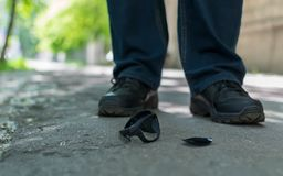 View of the feet of a man and broken sunglasses. View of the feet of a man who stands on an asphalt road on the background of fallen and broken sunglasses royalty free stock image