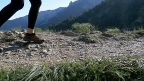 View on Feet of Traveler Woman Hiking Walking on the Top of Cliff in Mountain. Slow Motion. In 96 fps. Walking on Rocks. Camera follow hiker`s feet on top of stock video footage