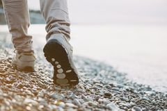 Walk on pebble coast. View of female legs walking on pebble coast near the sea royalty free stock images
