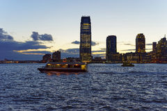 View on Ferry and Jersey City skyline in the evening Royalty Free Stock Image