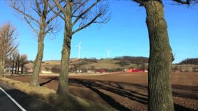 View of field against two wind turbines and small town in early spring. View from moving car in Poland stock video footage