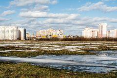 View of the field with a frozen pond and the outskirts of the city, new city under construction, spring sunny day stock photos