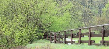 View of a field, a rail fence and a path. View of a field in the country including a wooden fence and a path Stock Image