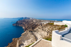 View of Fira town - Santorini island,Crete,Greece. White concrete staircases leading down to beautiful bay. With clear blue sky and sea Royalty Free Stock Photography