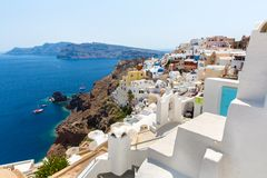 View of Fira town - Santorini island,Crete,Greece. White concrete staircases leading down to beautiful bay with clear blue sky Royalty Free Stock Photography