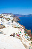 View of Fira town - Santorini island,Crete,Greece. White concrete staircases leading down to beautiful bay with clear blue sky Stock Image