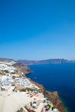 View of Fira town - Santorini island,Crete,Greece. White concrete staircases leading down to beautiful bay with clear blue sky and Stock Photo