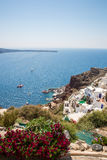 View of Fira town - Santorini island,Crete,Greece. White concrete staircases leading down to beautiful bay with clear blue sky and Royalty Free Stock Photos