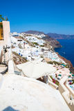 View of Fira town - Santorini island,Crete,Greece. White concrete staircases leading down to beautiful bay with clear blue sky and Stock Images