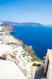 View of Fira town - Santorini island,Crete,Greece. White concrete staircases leading down to beautiful bay with clear blue sky and Royalty Free Stock Photography