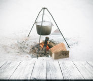 View on a fire in the snow from dark wooden gangway, table or br Stock Images