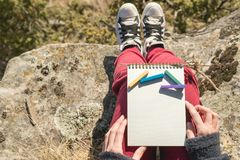 View from the first person on the female lap is a notebook with chalks for drawing pastels. Female hands holding a Stock Photos