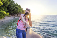 View from the first person of a man who holds a girl`s hand with a photo camera on the seashore. A view from the first person of a man who holds a girl`s hand Royalty Free Stock Images