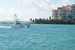 View from Fisher Island, Miami Beach, Florida. View of boat in blue waters from Fisher Island towards high rises of Miami Beach, Florida on sunny day royalty free stock photo