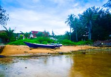 View of fisherman boat on the yellow sandy beach with coconut palm trees royalty free stock image